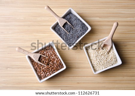 Flax, poppy and sesame seeds in little bowls on a wood table. - stock photo