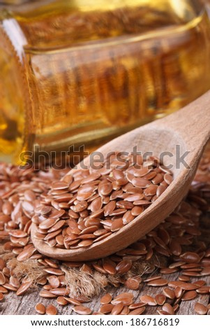 Flax seed in a wooden spoon on a background of the bottle with oil. vertical close up  - stock photo