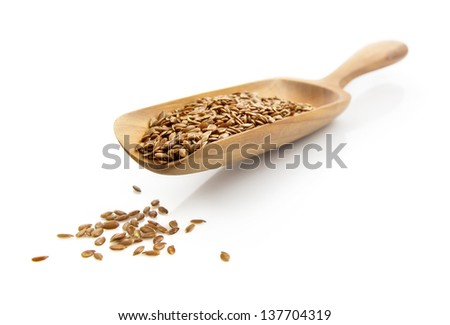 flax seed on spatula isolated on white background - stock photo