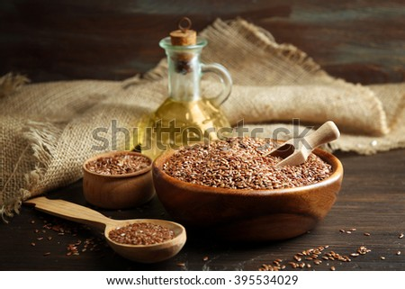 Flax seeds and oil on wooden table background, closeup - stock photo