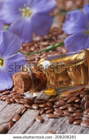 flax seeds, blue flowers and oil in the bottle macro on wooden background vertical  - stock photo