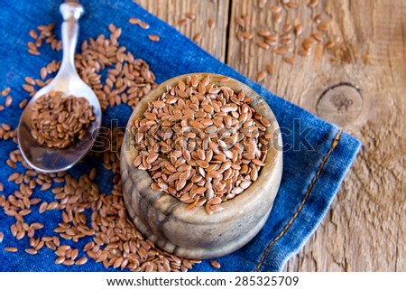 Flax seeds close up in bowl over napkin and rustic wooden table - stock photo