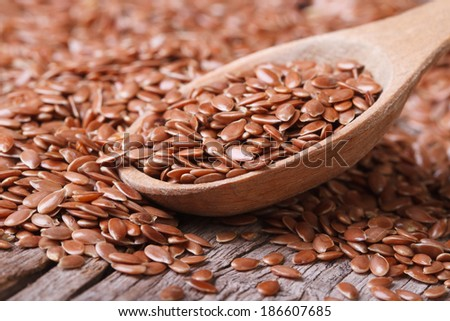 Flax seeds close up on a wooden spoon on a table. horizontal - stock photo