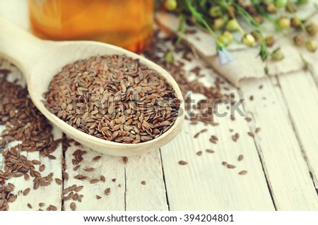 Flax seeds in spoon with linseed oil and linum plants, white wooden background - stock photo