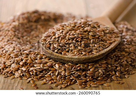 Flax seeds on a old  wooden spoon. Selective focus - stock photo