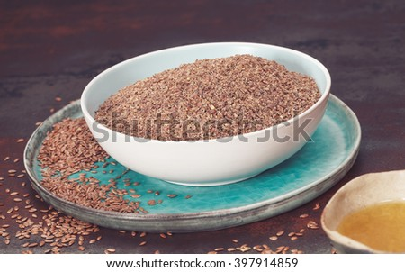 Flax seeds or linseed and oil.  Whole and ground flax seed with linseed oil. Macro, selective focus, vintage toned image - stock photo