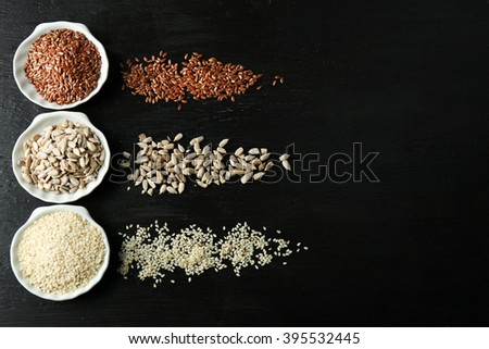 Flax, sesame and sunflower seeds on wooden table - stock photo