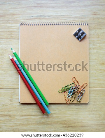 Flay lay notebook, pencils and paperclips for a school theme.