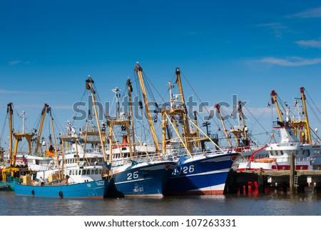fleet of fish trawlers in the harbor - stock photo