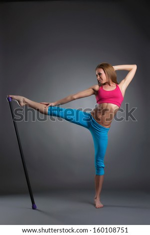 Flexible athletic model posing with fitness bar - stock photo