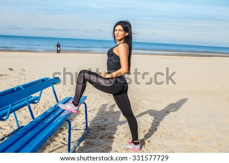 Flexible brunette woman in sportswear doing gymnastic exercises on a beach over blue sky. - stock photo
