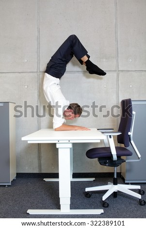 flexible business man in scorpion asana on desk in his office - profile view - stock photo