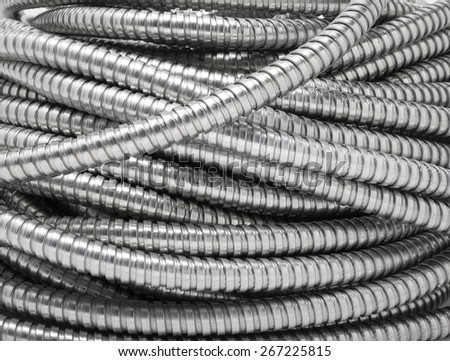 Flexible metal pipe on a white background. - stock photo