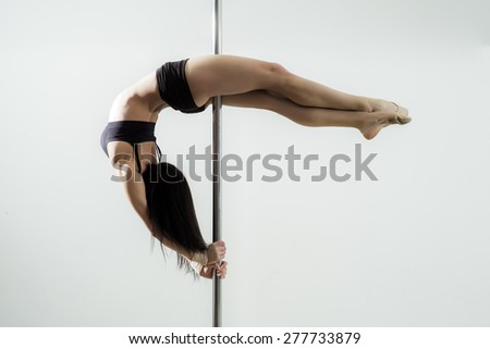 Flexible sexy girl dancing in black lingerie on the pole on white background copyspace, horizontal picture - stock photo