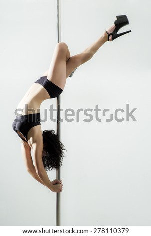 Flexible sexy woman dancing in black lingerie on the pole on white background copyspace, vertical picture - stock photo
