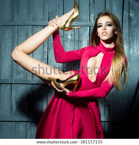 Flexible straight young fashionable woman with long beautiful hair in red elegant dress holding raised leg in glamour golden shoes on wooden background, square picture