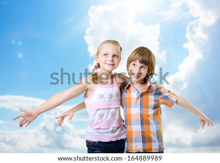 Fliers. Kids play and have fun together. Children playing fly over blue sky with clouds - stock photo