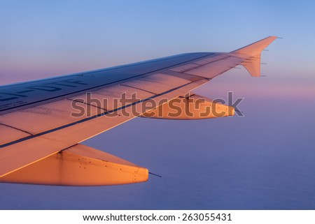 Flight at sunrise. The wing of the plane and the sky lit with beams of a rising sun. Plane view from the window - stock photo
