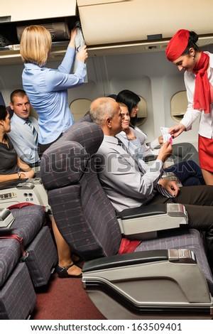 Flight attendant check passenger tickets in plane cabin - stock photo