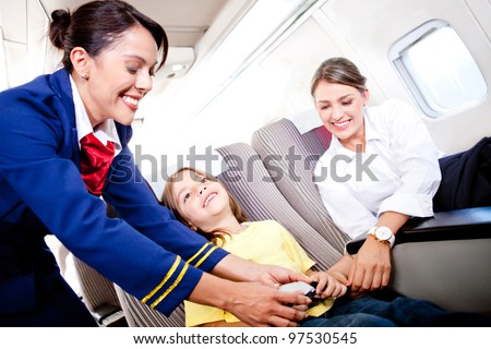 Flight attendant fastening seat belt to boy for a safe trip - stock photo