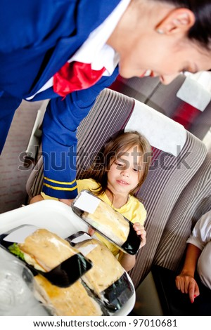 Flight attendant serving food to a kid in the airplane - stock photo