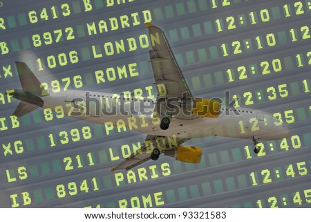 Flight Board and Airliner Landing at the Airport - stock photo