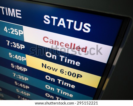 Flight cancelled. Airport arrival and departure board sign showing on-time and cancelled flight status - stock photo