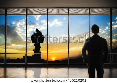 Flight control tower with twilight sky sunset on a big window and backside of business man standing in front of window - stock photo