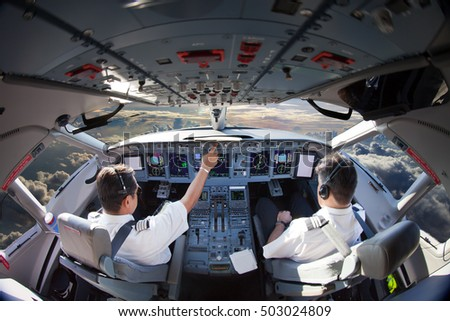 Flight Deck of modern passenger aircraft. Cockpit view in flight during the sunset. Aircraft Pilots at work.