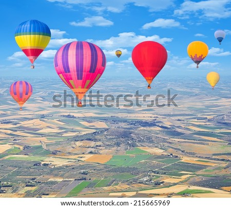 Flight of hot air balloons above the countryside.  - stock photo