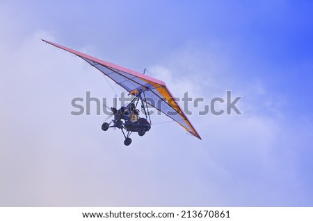 Flight of the motor deltaplane above the clouds. - stock photo