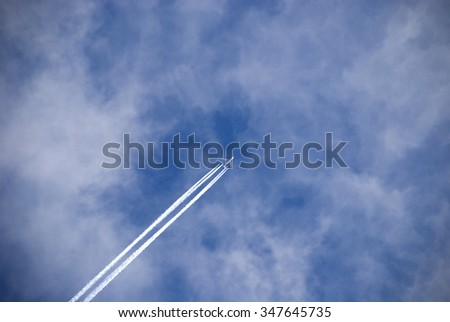 Flight of the passenger plane against white clouds.