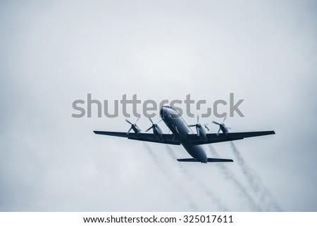 Flight of the retro passenger plane at sunset time. - stock photo