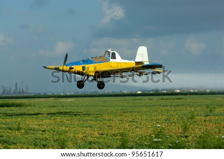 flight of the yellow agricultural airplane - stock photo