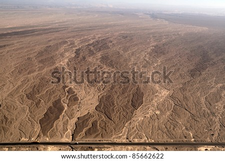 Flight over Nazca lines - Dry river bed aerial view with a road - Peru