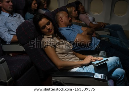 Flight passengers sleeping plane cabin night travel - stock photo