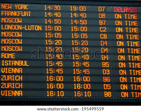 Flights information board with arrivals and departures details  in an international  airport terminal - stock photo