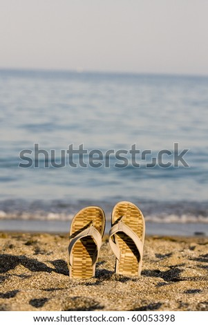 flip flop on sandy beach in front of the sea - stock photo