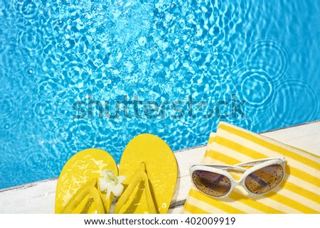 Flip flop,towel and sunglasses on the side of a swimming pool - stock photo
