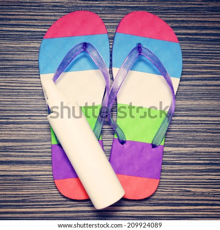 Flip flops and Bottle with suntan cream on wooden floor. Summer vacations background
