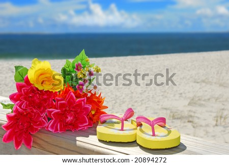 Flip flops and bouquet on beautiful beach by ocean - stock photo