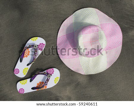 Flip-flops and hat on the black sand of Tenerife island, Canaries - stock photo
