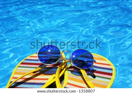 Flip flops and sunglasses by bright blue pool water