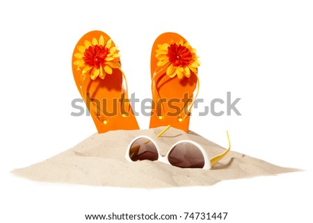 flip-flops and sunglasses on a sunny part of the beach - stock photo