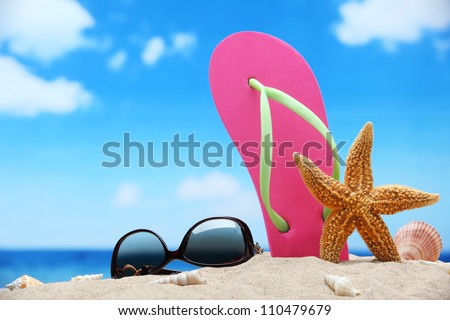 Flip-flops and sunglasses on sand beach. - stock photo