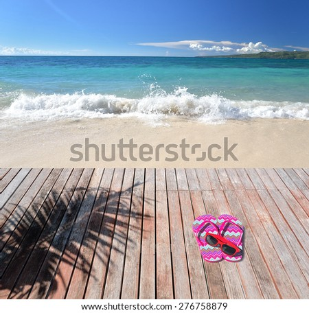 Flip flops and sunglasses on the wooden platform beside tropical beach  - stock photo