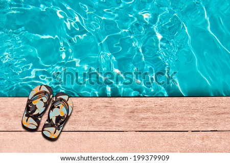 Flip flops and swimming pool close-up - stock photo