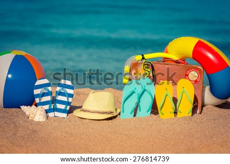 Flip-flops, beach ball and vintage suitcase on the sand. Summer vacation concept - stock photo