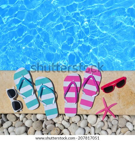 Flip flops, glasses and starfish by the poolside  - stock photo