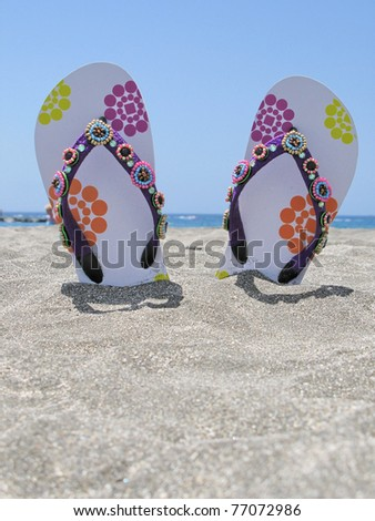 Flip-flops in the black sand of Tenerife island, Canaries - stock photo